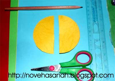Selanjutnya, guntinglah kertas berbentuk lingkaran tersebut. Dan, kita hanya membutuhkan setengah lingkaran saja untuk membuat ujung roket kertas.