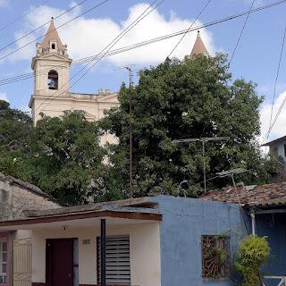 Kuba, Matanzas, Türme der Iglesia de San Pedro Apostol in Versalles ragen halb verdeckt von belaubten Bäumen, davor schäbige Wohnbebauung.