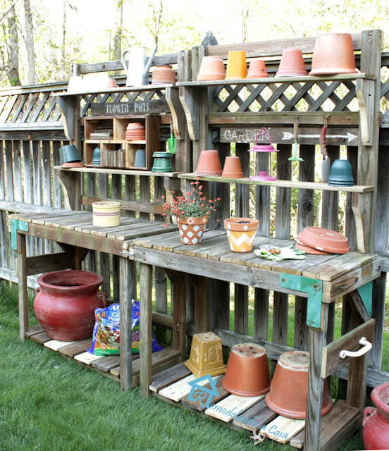 wooden potting benches with lots of pots and watering cans on it.