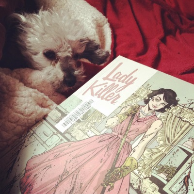 Murchie pokes his head out of a red blanket cave. Directly in front of him is a trade paperback copy of Lady Killer. Its cover features a very thin brunette white woman wearing a pink A-line dress splattered in blood. She stands in a similarly bloodspattered kitchen and holds a mop.