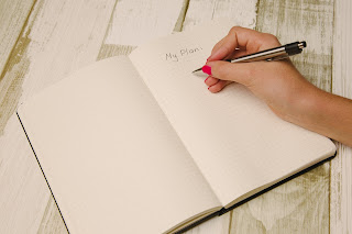 A hand preparing to write the design for a game on a page in a notebook that has the words 'My Plan' written across the top.