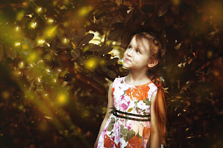 niña pelirroja en un bosque mirando luciérnagas