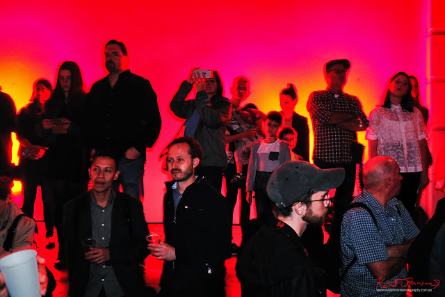 HeadOn Photo Festival launch in Paddington Sydney - Crowd portrait in deep red lighting reminiscent of being in a black and white print processing darkroom. Photo by Kent Johnson for Street Fashion Sydney.