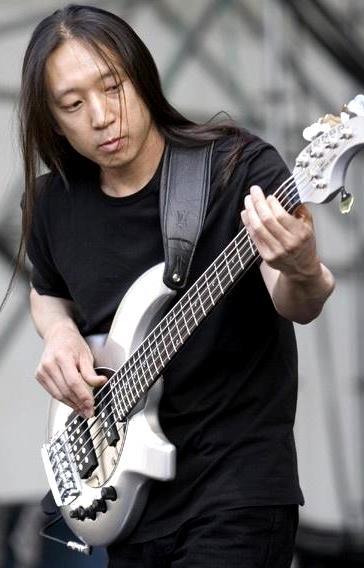 Foto de John Myung tocando concentrado en concierto
