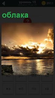Над водной гладью проплывают облака и уходят за горизонт закрывая собой солнце