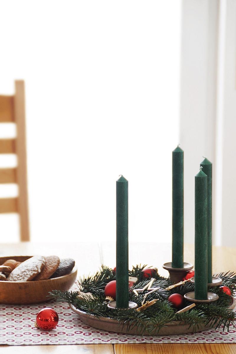 Weihnachtsdeko Adventskranz klassisch traditionell modern in rot, weiß, grün, Holz. Tannengrün, dekoriert mit Baumkugeln und Sternen, Tischläufer, Esstisch dekorieren, Holzschale mit Plätzchen. Tasteboykott Blog Interior.