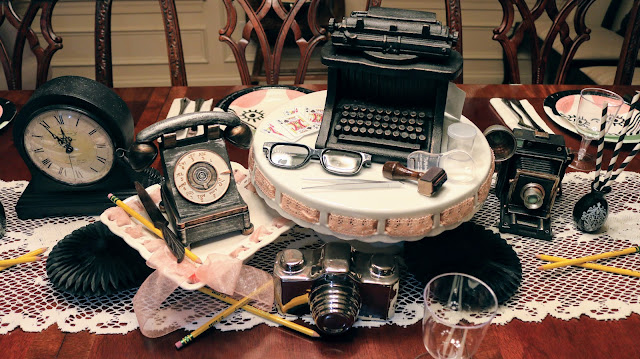 Vintage Spy decorations on a table - clock, pencils, vintage phone, camera, letter opener