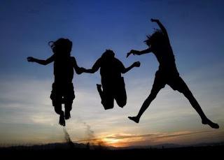 Tres niños saltando con la puesta de sol de fondo