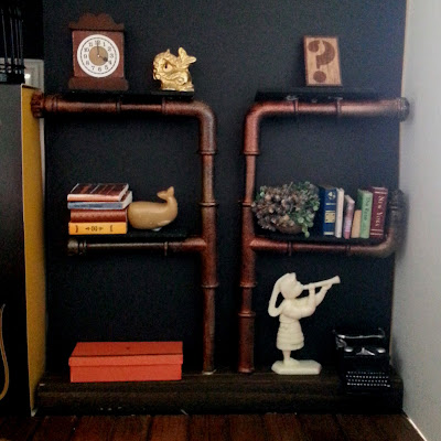 One-tweltfh scale modern miniature pipe shelving mounted on a length of wood, with various miniatures displayed on the shelves and wood surface.