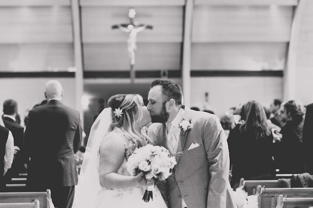 bride and groom kissing at st. pauls catholic church in clinton township michigan