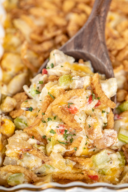 scooping hot chicken salad out of casserole dish
