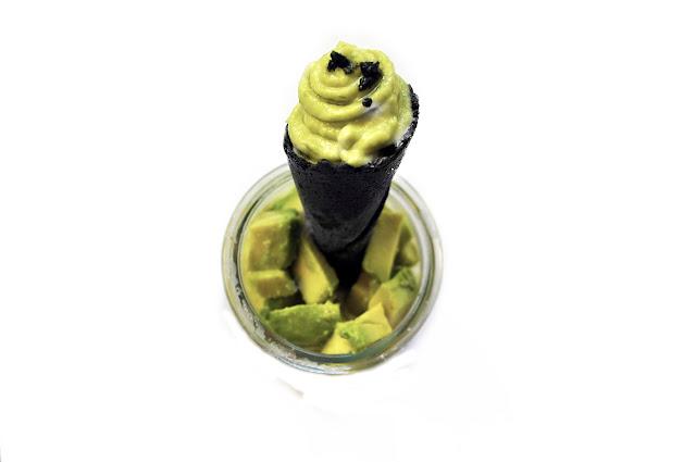 relleno de una pasta verde con unos granitos de sal negra, sobre cubos de aguacate