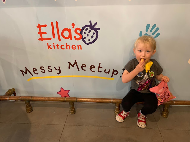 "A poster saying ""Ella's Kitchen Messy Meetups"" and a toddler eating some food witha toy banana stuffed down her t-shirt"""