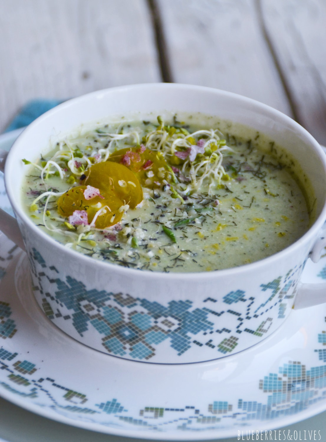 cold raw soup in vintage colorful porcelain bowl, blue tablecloth, yellow tomatoes