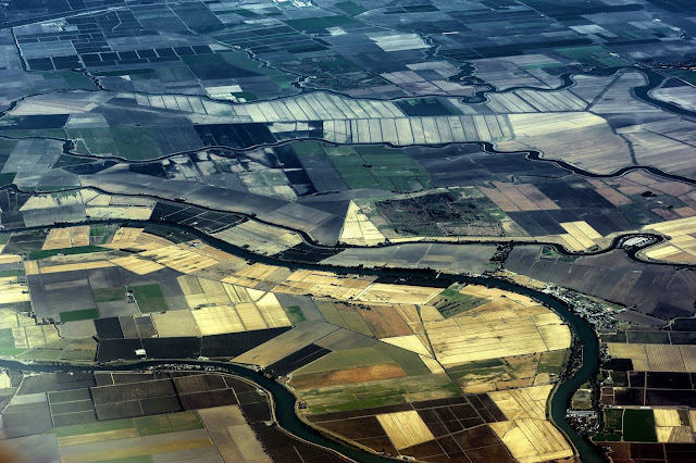 An aerial look at a river, and plots of land below.