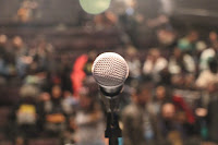 Close up image of a microphone on a stage. The audience that is facing the microphone is blurred, appearing as a myriad of colors (red, white, green, yellow, etc.)