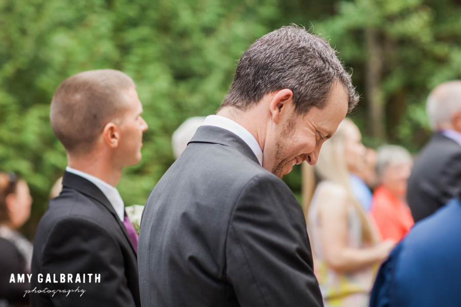 groom reacting with a smile when he sees his bride