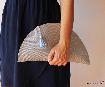 Imagen que muestra una cartera de mano de rafia, ideal para bodas, en gris con borla azul lavanda.