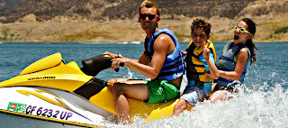 Camp counselor giving two campers (a boy and a girl) a jet ski ride at summer camp.