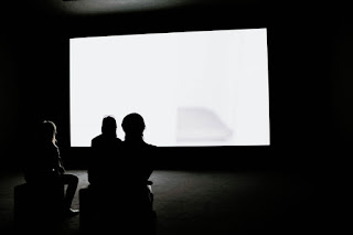 Three people looking at a screen