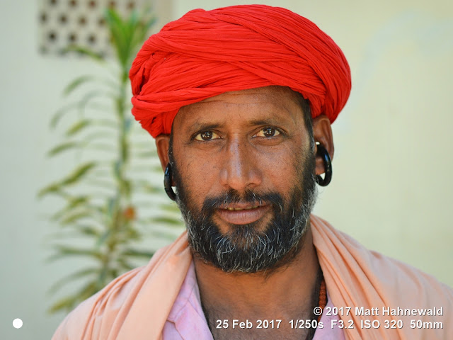 matt hahnewald photography; facing the world; gorakh nath; monk; monastery; bhavnath; bhavnath fair; character; face; earrings; ears; holed; eyes; facial expression; eye contact; full beard; turban; orange; consent; empathy; rapport; respect; traveling; religious; traditional; cultural; hinduism; festival; event; mela; devotee; pilgrim; junagadh; gujarat; asian; indian; western india; one person; male; middle-aged; man; picture; photo; face perception; physiognomy; educational; nikon d3100; nikkor af-s 50mm f/1.8g; prime lens; 50mm lens; 4x3 aspect ratio; horizontal orientation; street; portrait; closeup; headshot; seven-eighths view; outdoors; color; posing; authentic; smiling; powerful; determined; manly; kanphata; yogi; darshani; gorakhnathi; shaivism; red; splitted ears
