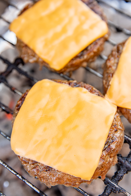 hamburgers topped with cheese cooking on a grill