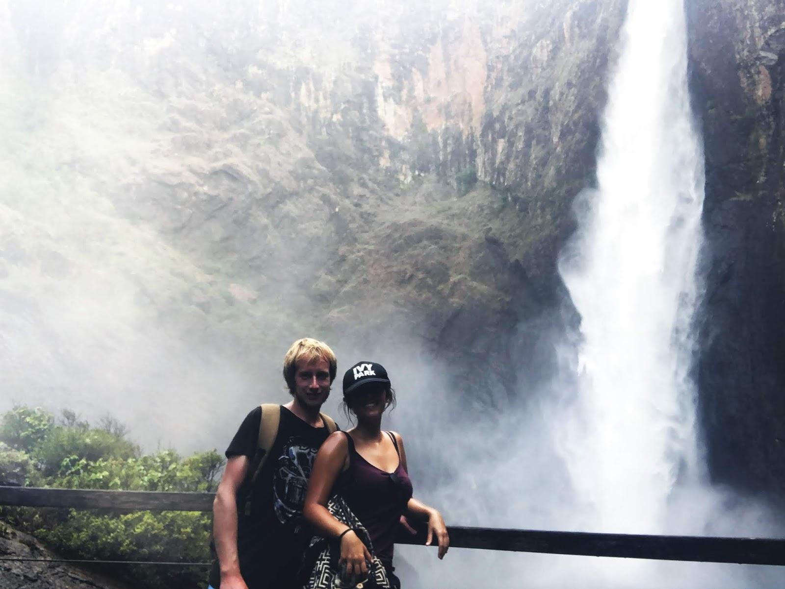 Dolny punkt widokowy na wodospad Wallaman Falls, który znajduje się za dwoma podróżnikami. Dwie osoby mężczyzna i kobieta zwróceni są w stronę kamery żeby zrobić sobie turystyczne zdjęcie.