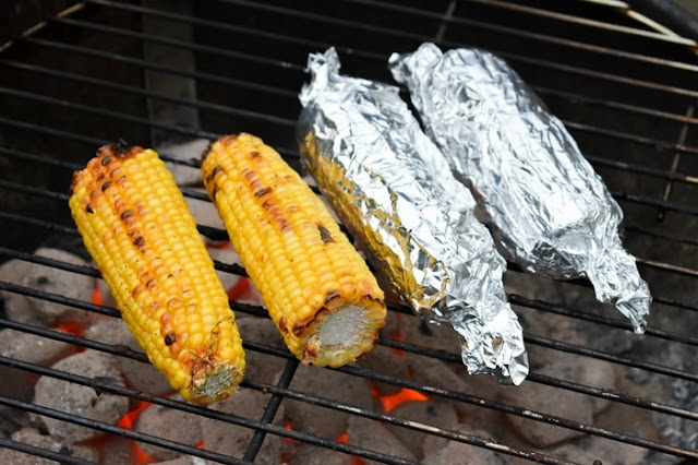 Well cooked naked corn and corn on the cob in foil on the barbecue