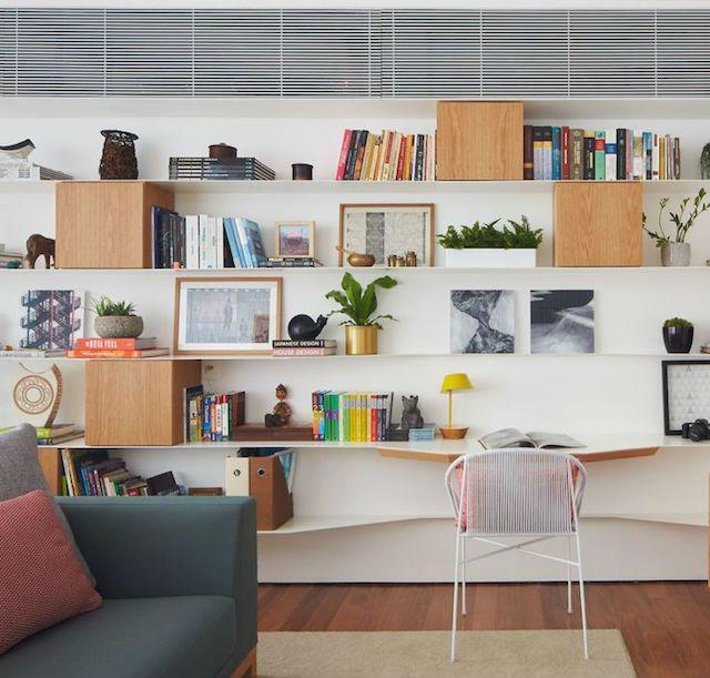 Zona de trabajo en el salón con estanterías voladas, cubos y tablas curvas