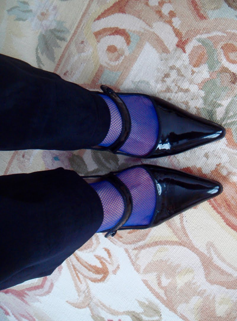 Up close of black patent maryjanes with blue fishnet socks.