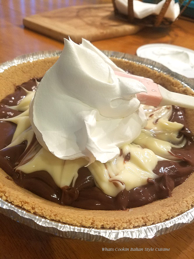 This is a fudge marble pudding pie made with vanilla and chocolate pie filling in a graham cracker crust.