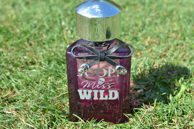 Image of the Miss Wild fragrance sitting on the grass
