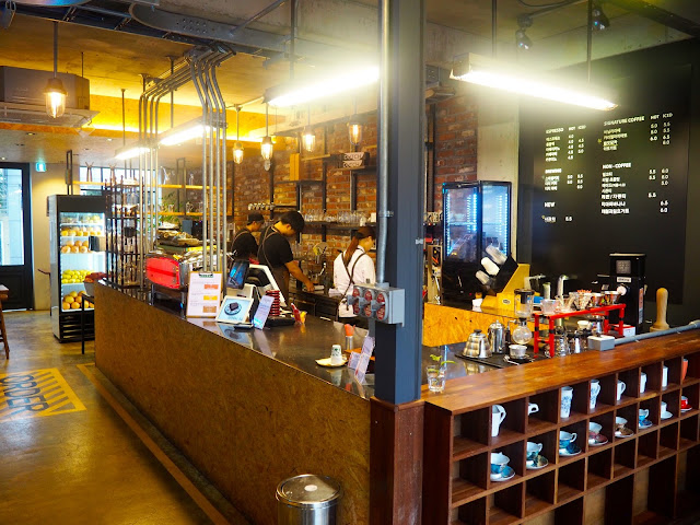 Cafe interior - barista brewing station, menu and shelves of cups inside Red Velvet Cafe in Myeongnyun, Busan, South Korea