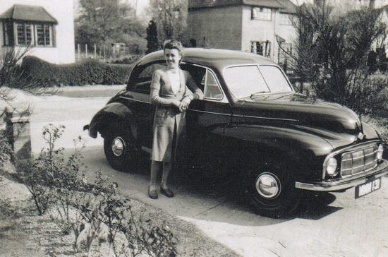 Photograph of the front garden at 51 Bradmore Way showing houses opposite. My mother with our Morris Minor Image courtesy of Judy Marchsnt