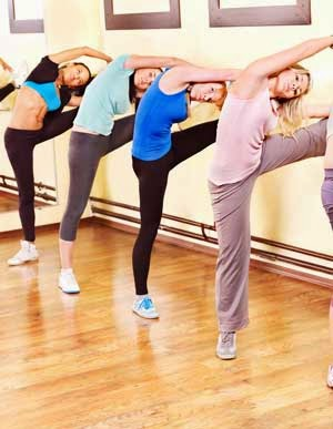 Women doing a ballet bar workout at the gym
