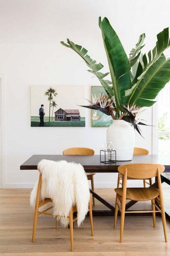 10 formas de veranizar tu casa con guiños tropicales; comedor con centro de mesa de hojas grandes
