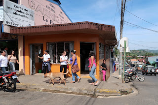 group of people and a dog on busy street corner in Puriscal