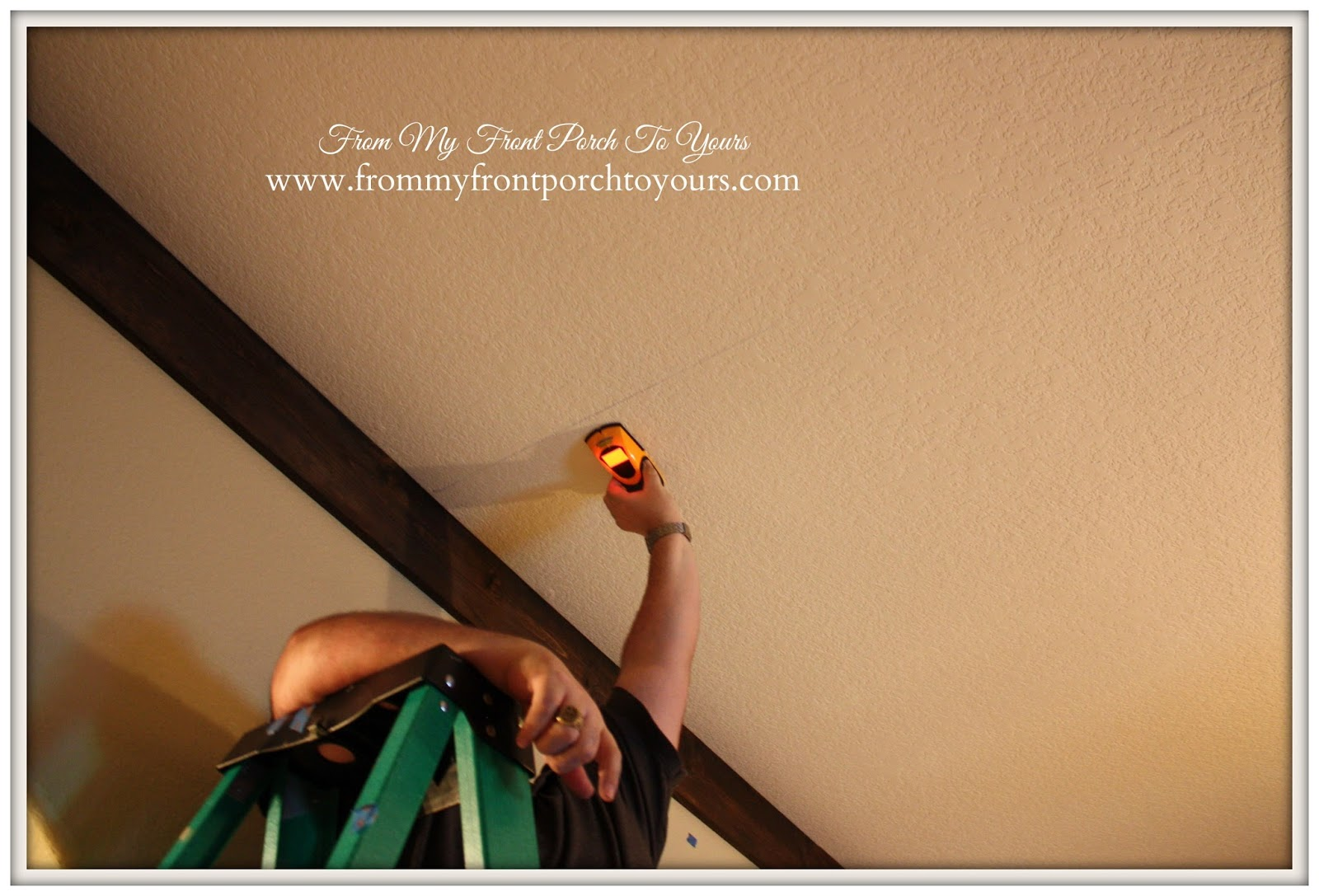 Using a stud finder to ensure wood beams will be secure when installed on the ceiling at From My Front Porch To Yours.