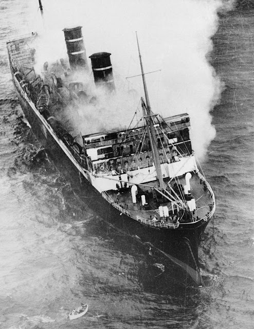 Smoke billows from the burning midsection of the ship as it drifts toward shore.