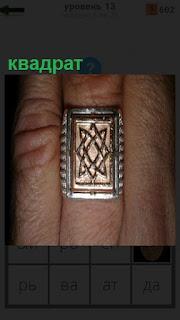 На пальце руки одет перстень в виде квадрата с рисунком