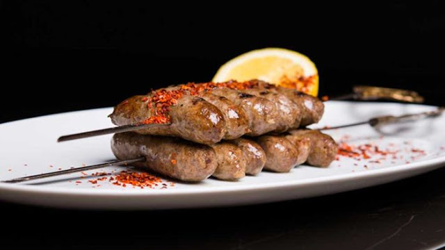 Grilled lamb sausages with skewers in a serving dish Skewered house-made Lebanese style lamb sausages with Turkish chilli flakes recipe