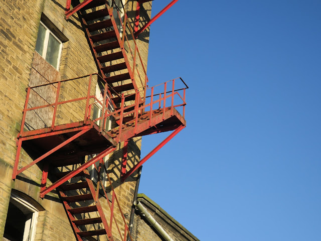 Red iron fire-escape on derelict mill with blue winter sky.