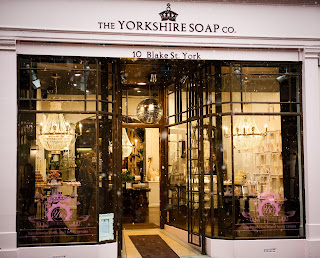 A square pink brick store with Yorkshire Soap Company in black simple font with rectangular glass windows filled with pink balloons on a bright white background