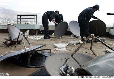 Iranian police officers dismantle illegal rooftop satellite dishes