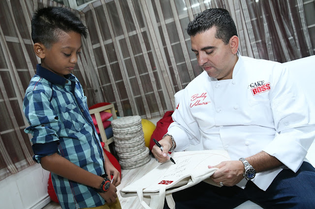 Fathul of the Make A Wish Foundation getting his exclusive autographed TLC bag from Buddy Valastro