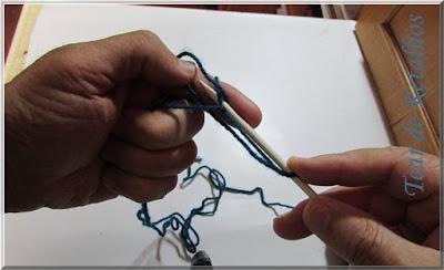 Foto mostrando a retirada do dedo polegar do ponto e deixando o ponto na agulha na montagem à italiana