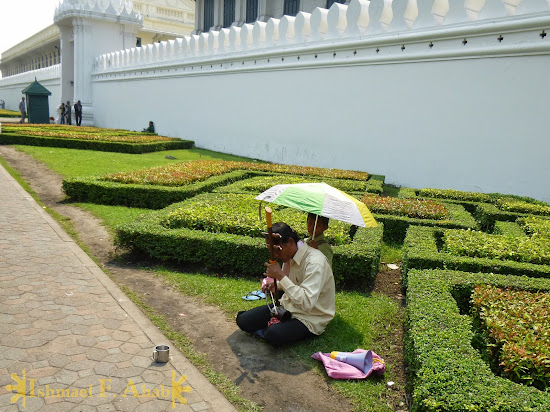 Musician-beaggar outside the walls of Grand Palace, Bangkok