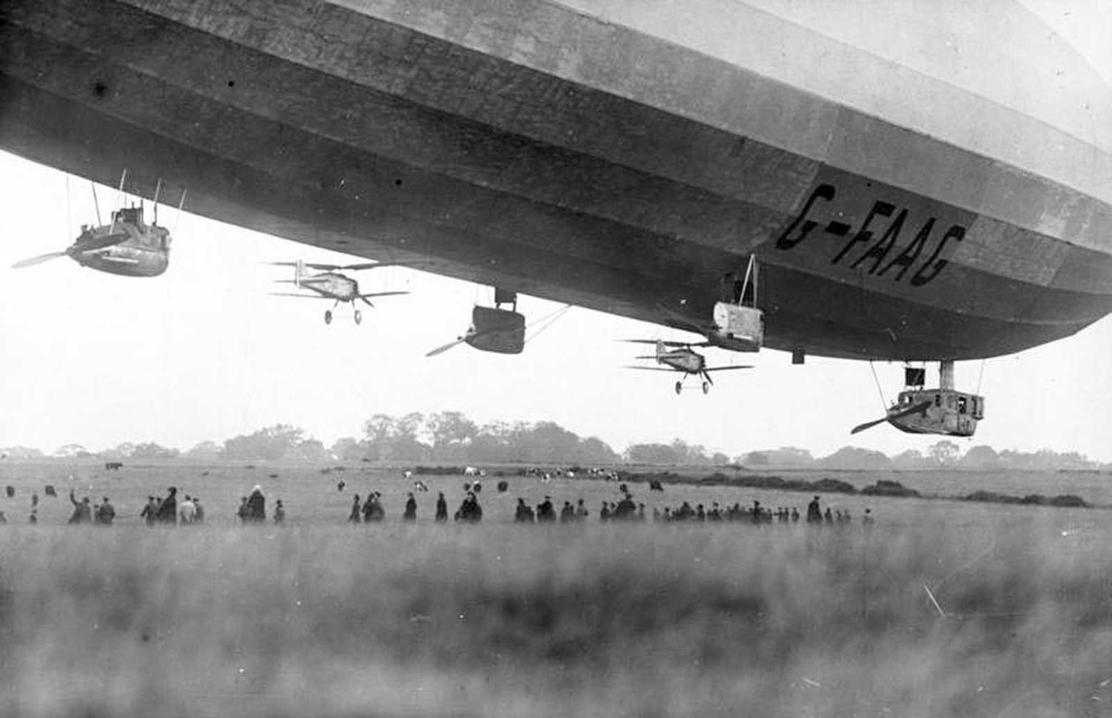 A pair of Gloster Grebe fighter planes, tethered to the underside of the British Royal Navy airship R33, in October of 1926.