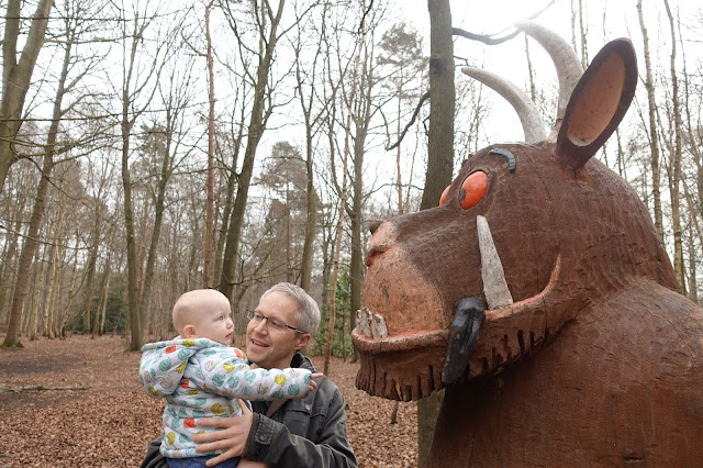 A baby held by her daddy is looking at a carved gruffalo with a black tongue