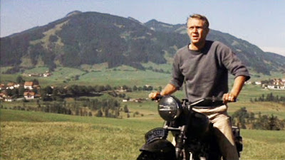 Fotograma de La gran evasión con Steve McQueen subido en una moto, al fondo un paisaje de campiña con suaves elevaciones y un pueblo al fondo